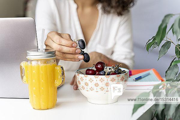 Nahaufnahme einer Frau am Schreibtisch mit Orangensaft  die Früchte aufhebt