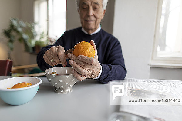 Älterer Mann schält zu Hause Orangen