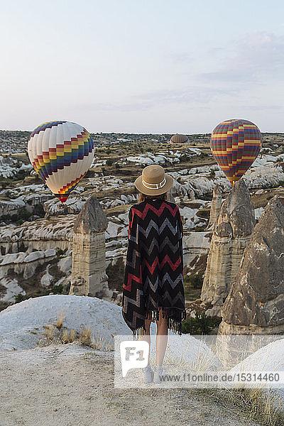 Junge Frau und Heißluftballons am Abend  Goreme  Kappadokien  Türkei