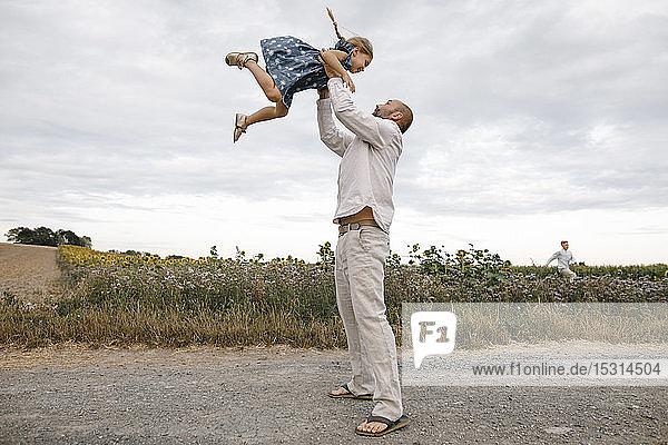 Vater spielt mit seiner Tochter  hält sie in die Höhe