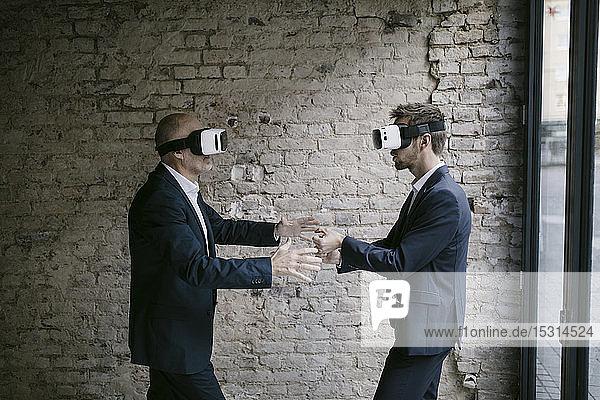 Älterer und mittel-erwachsener Geschäftsmann mit VR-Brille