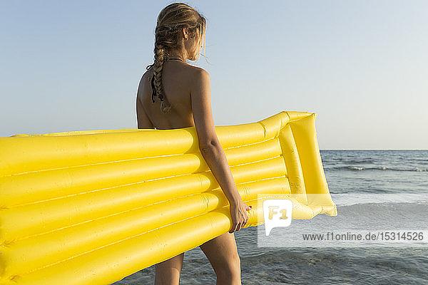 Rückansicht einer jungen Frau mit gelbem Luftbett am Strand  Blick in die Ferne