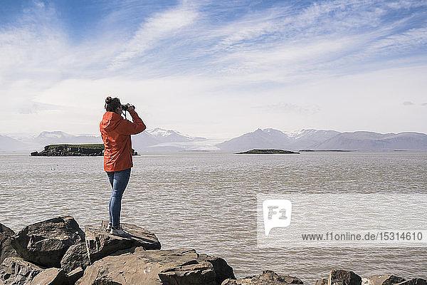 Junge Frau steht auf Felsblöcken und schaut durch ein Fernglas  Südost-Island