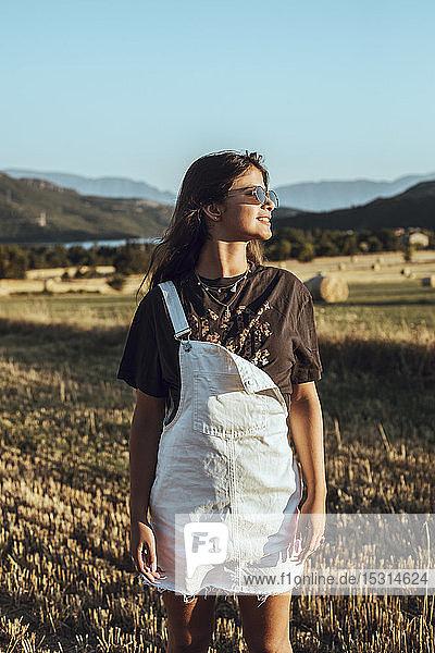 Lächelnde junge Frau steht bei Sonnenuntergang in Feldlandschaft