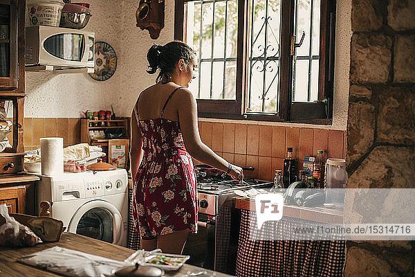 Rückansicht einer Frau beim Kochen in der Küche