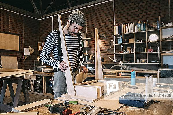 Zimmermann bei der Arbeit am Holztisch Zimmermann bei der Arbeit am Holztisch