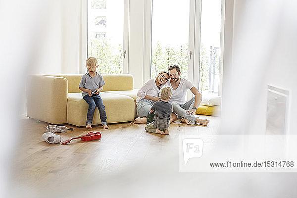 Glückliche Familie mit zwei Söhnen  die im Wohnzimmer ihres neuen Zuhauses spielen