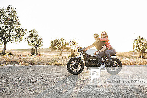 Portrait of couple sitting on motorbike at evening twilight