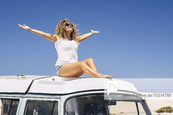 Frau sitzt auf dem Dach eines Lieferwagens mit erhobenen Armen