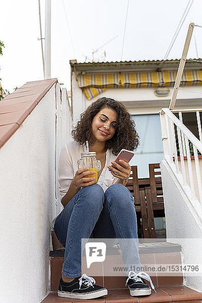 Lächelnde junge Frau auf der Treppe sitzend mit Zelle und Orangensaft