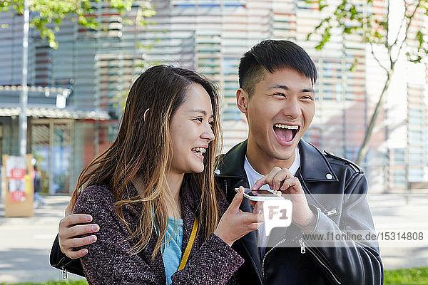 Glückliches Paar schickt eine Sprachnachricht mit dem Handy  Barcelona  Spanien