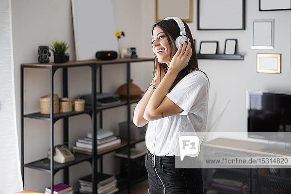 Happy young woman listening to music with headphones at home