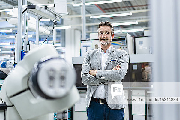 Portrait of confident businessman at assembly robot in a factory
