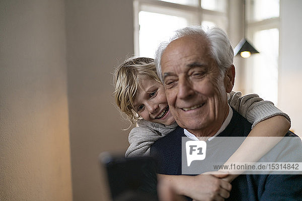 Glücklicher Enkel umarmt Großvater mit Handy zu Hause