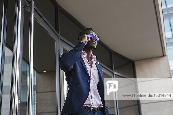 Young businessman using his smartphone outside