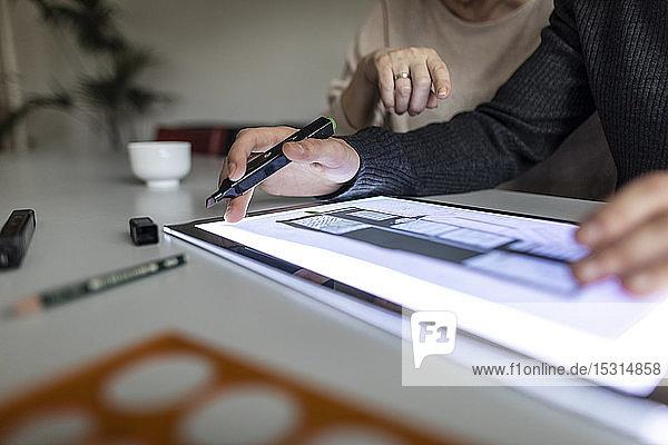 Nahaufnahme eines Mannes mit Tablett mit Architekturplan