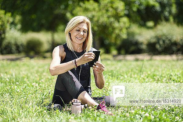 Reife Frau  die ihr Smartphone benutzt und sich nach dem Sport im Gras eines Parks ausruht