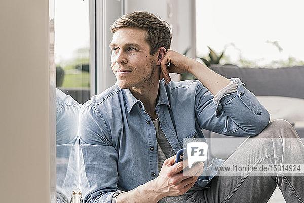 Mittelgroßer erwachsener Mann am Fenster sitzend  mit Smartphone