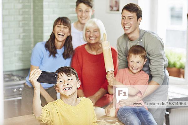 Junge  der von sich und seiner Familie Besitz ergreift und zu Hause Pizza zubereitet
