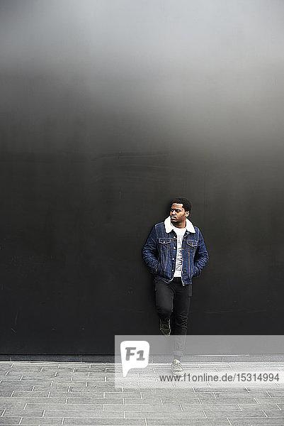 Mann in Jeansjacke vor dunklem Hintergrund stehend