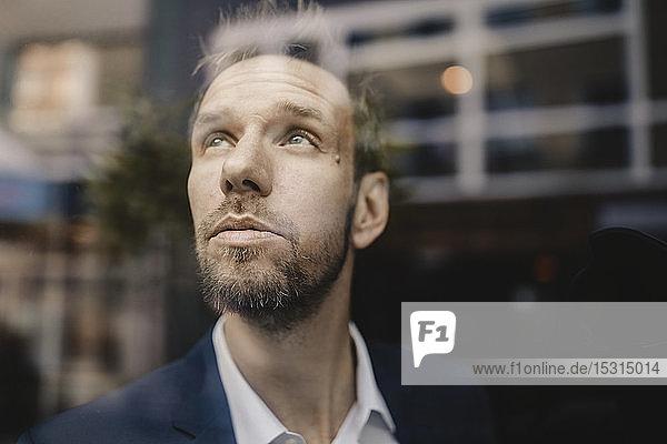 Porträt eines Geschäftsmannes  der aus dem Fenster schaut