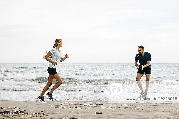 Joggerin mit ihrem Trainer am Strand