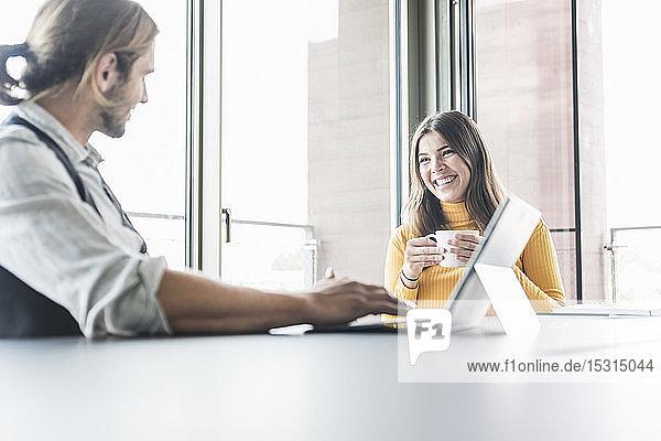 Junge Geschäftsfrau und Geschäftsmann sitzen am Schreibtisch im Büro und unterhalten sich