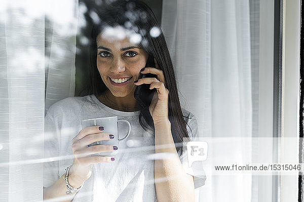 Portrait of smiling young woman on cell phone behind windowpane