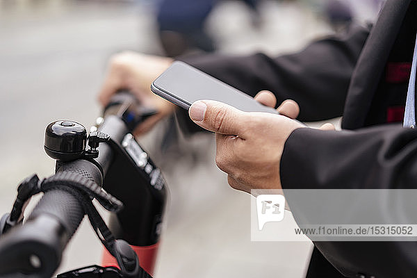 Close-up of businessman with e-scooter using cell phone
