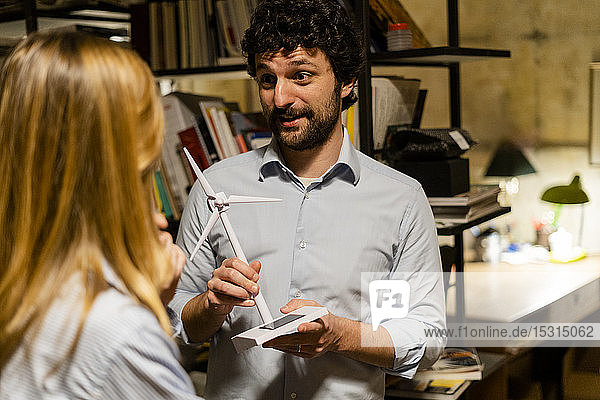 Businessman with wind turbine model talking to colleague in office