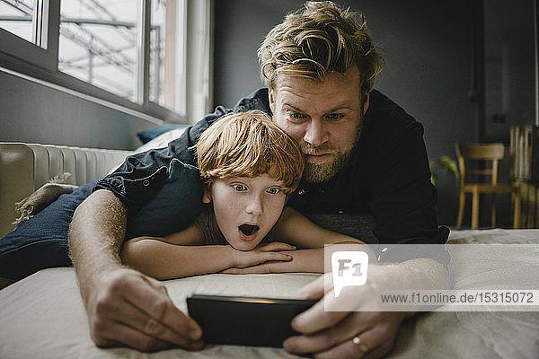 Porträt von Vater und Sohn  die auf der Couch liegen und auf ein Handy schauen