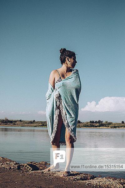 Junge Frau in ein Handtuch gewickelt am Seeufer stehend