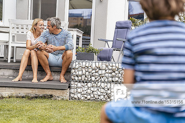 Happy parents sitting on steps in garden with boy in foreground