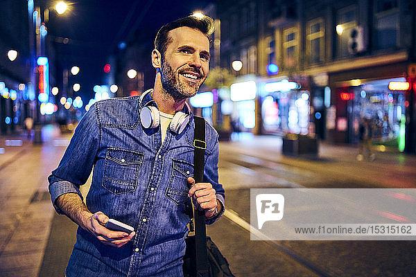 Lächeln mit Smartphone in der Stadt in der Nacht beim Warten auf die Straßenbahn