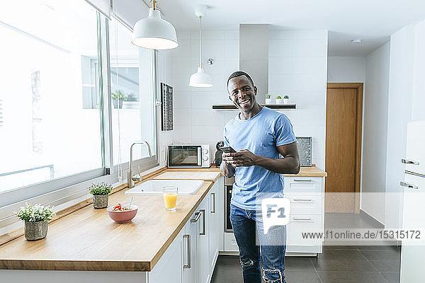 Porträt eines glücklichen jungen Mannes  der zu Hause in der Küche ein Handy benutzt