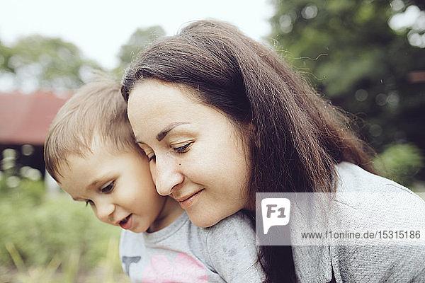 Anhängliche Mutter mit Kleinkind im Garten