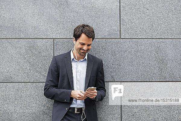 Lächelnder Geschäftsmann mit Kopfhörern  der auf sein Mobiltelefon schaut