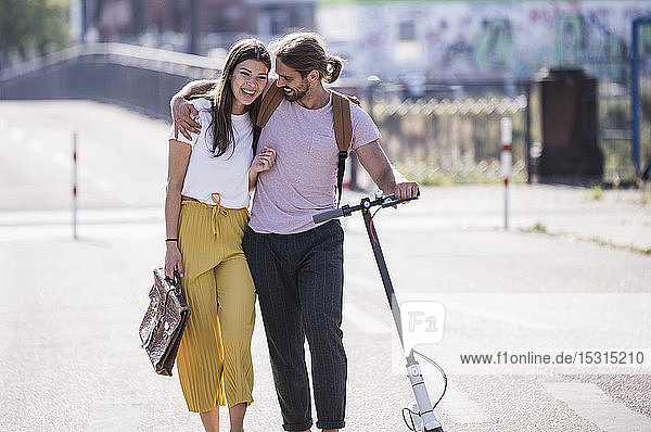 Young couple with electric scooter walking on the street