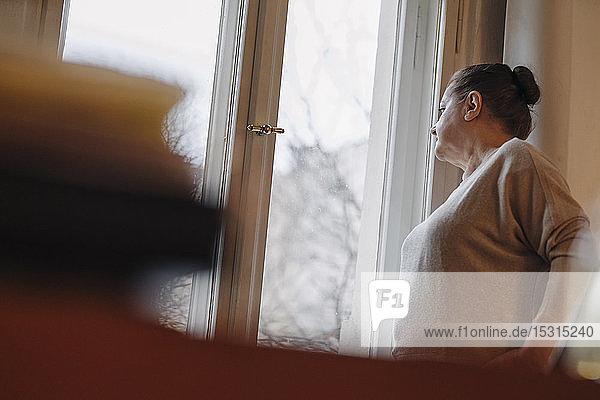 Seriöse ältere Frau  die zu Hause aus dem Fenster schaut