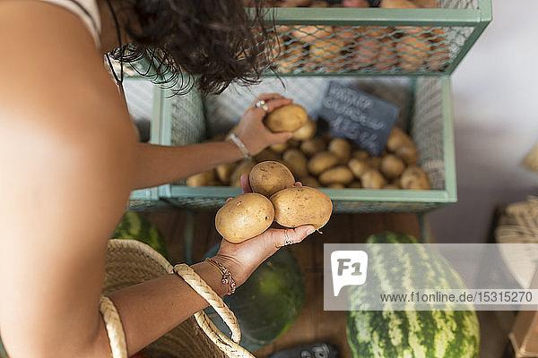 Junge Frau im Bioladen bei der Kartoffelauswahl Junge Frau im Bioladen bei der Kartoffelauswahl