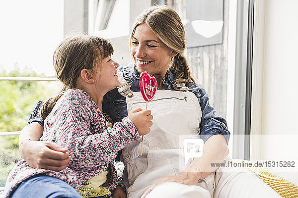 Happy mother and daughter with lollipop at the window at home