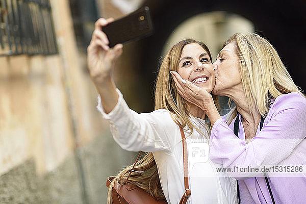 Glückliche Frau  die mit ihrer Mutter in der Stadt ein Selfie mitnimmt