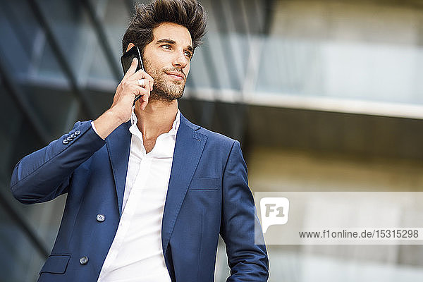Businessman talking on cell phone outside an office building