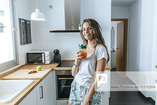 Portrait of smiling young woman having a drink in the kitchen