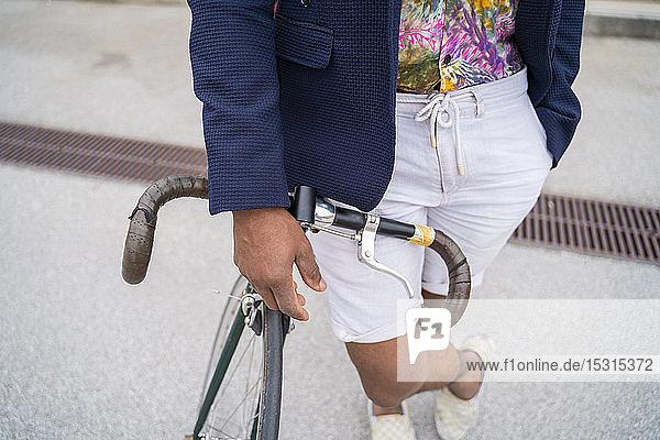 Nahaufnahme eines stilvollen Mannes  der sich auf ein Fahrrad lehnt