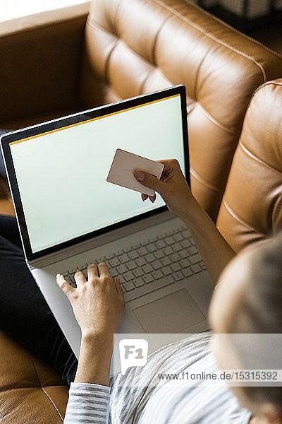 Junge Frau auf der Couch zu Hause beim Online-Shopping