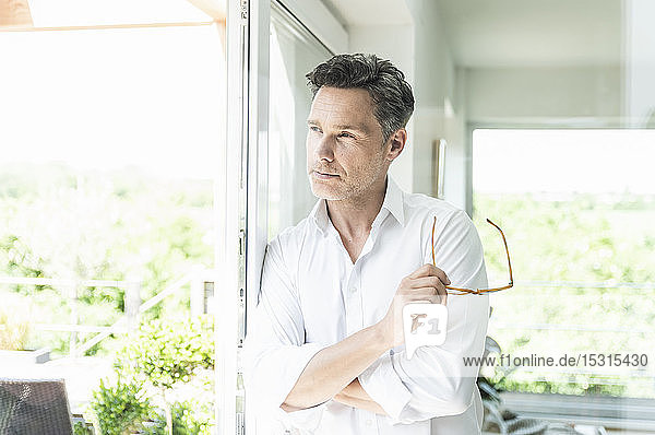 Mature man leaning on window  holding his spectacles