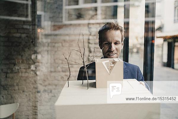 Lächelnder Geschäftsmann mit Architekturmodell
