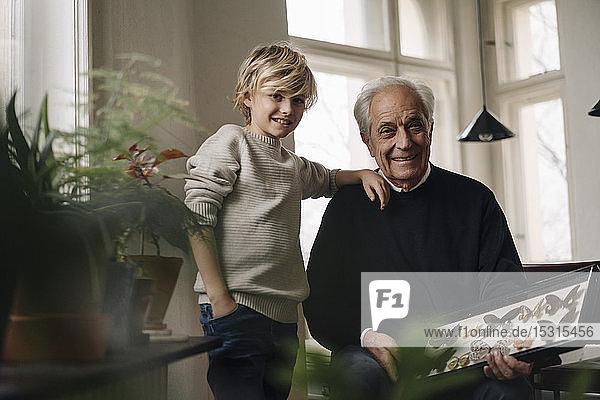 Großvater zeigt Enkel zu Hause Schmetterlingssammlung