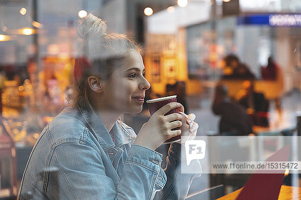 Young woman in a cafe drinking and enjoying a coffee